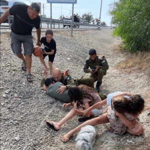 Col. Sagi Baruch, head of the IDF Home Front Command's Southern District shielding a child on the side of the road while sirens signalincoming rocketson Sunday